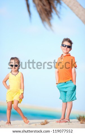 Brother and sister at beautiful white sand beach - stock photo
