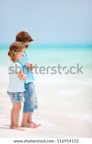 Brother and sister at tropical beach - stock photo