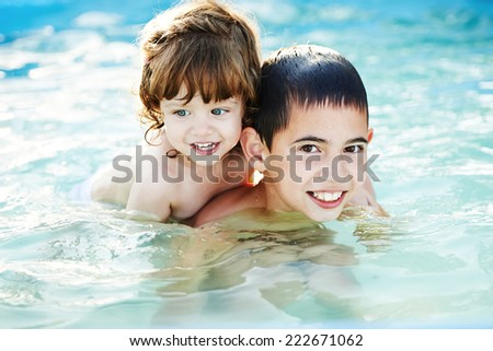 brother and sister bathe outside in pool - stock photo