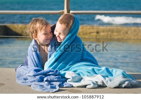 Brother and sister cuddling in a towel after a swim at the beach - stock photo