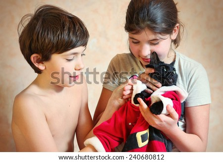 brother and sister dress their black cat in santa costume - stock photo