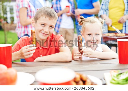 Brother and sister eating sausages outdoors with parents on background