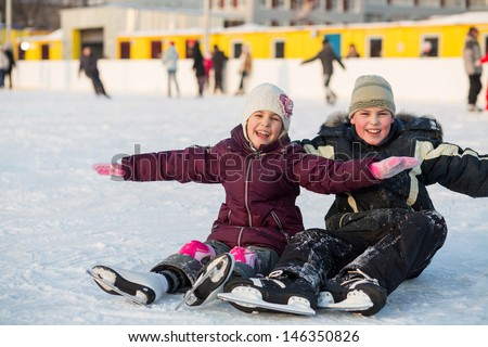 Brother and sister fell while skating and having fun on the ice - stock photo