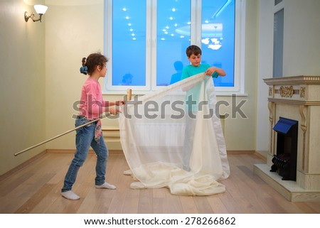 Brother and sister hanging curtains in new apartment in evening  - stock photo