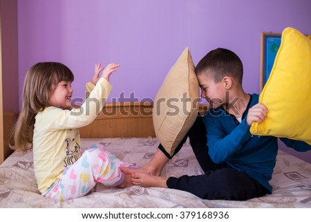 Brother and sister having fun in a pillow fight. Little boy is holding a pillow, while the girl  hits him with her pillow. Both are wearing their pajamas / Happy children in a pillow fight - stock photo