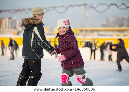 Brother and sister having fun skating on the rink - stock photo