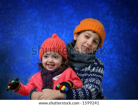 Brother and sister having fun with the snow in winter outfit.