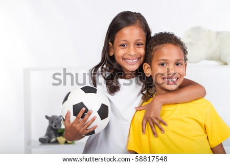brother and sister holding a soccer ball - stock photo