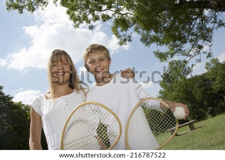Brother and sister holding tennis rackets. - stock photo