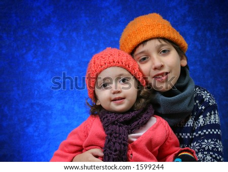Brother and sister hugging in winter outfit.