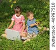 Brother and sister in a garden with a laptop - stock photo