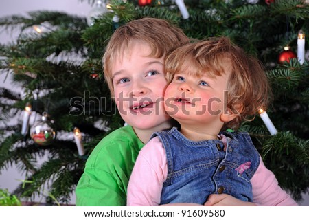 brother and sister in front od christmastree