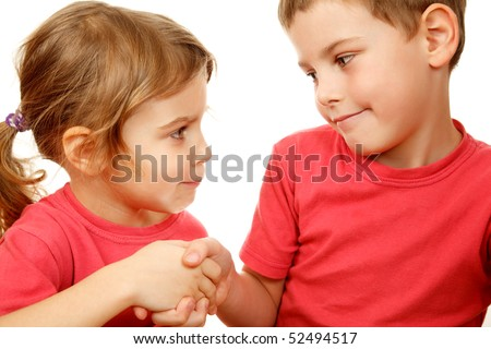 Brother and sister in pink shirts with smile shake hands. Fake smile, bad peace is better than a good war. - stock photo