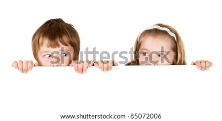 Brother and sister looking each other and  holding empty white board - stock photo