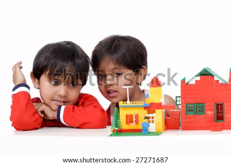 brother and sister observing houses of blocks - stock photo