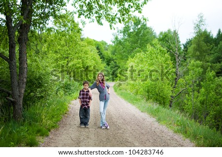 brother and sister on a trail outdoors in summer - stock photo