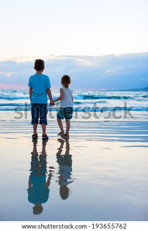 Brother and sister on beach at sunset - stock photo