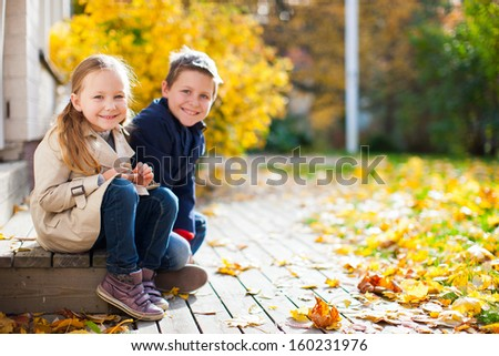 Brother and sister outdoors at beautiful autumn day - stock photo