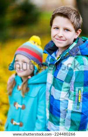 Brother and sister outdoors in a beautiful park at sunny autumn day - stock photo