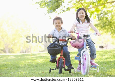 Brother and sister outdoors on bicycles smiling - stock photo