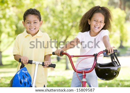 Brother and sister outdoors with scooter and bicycle smiling - stock photo