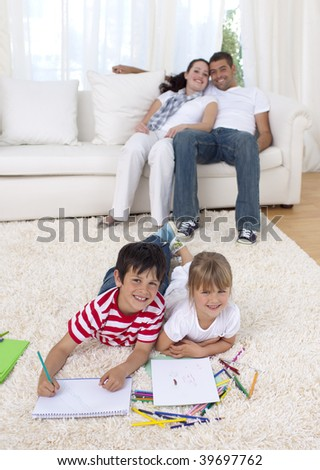 Brother and sister painting on floor in living-room with their parents on sofa - stock photo