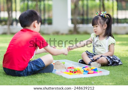 brother and sister play sand - stock photo