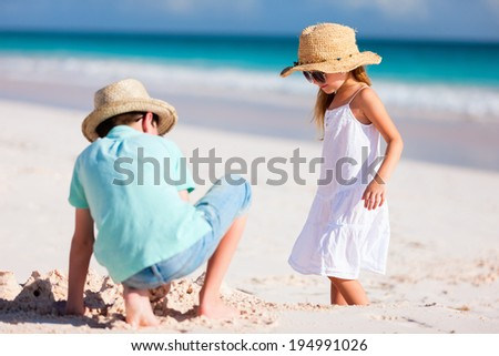 Brother and sister playing and having fun at beach on summer vacation - stock photo