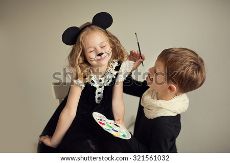 Brother and sister playing at artist and model. Face painting, - stock photo