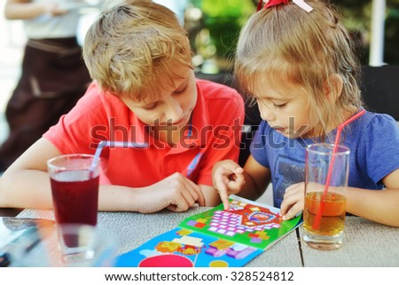 brother and sister playing game in outdoor cafe - stock photo