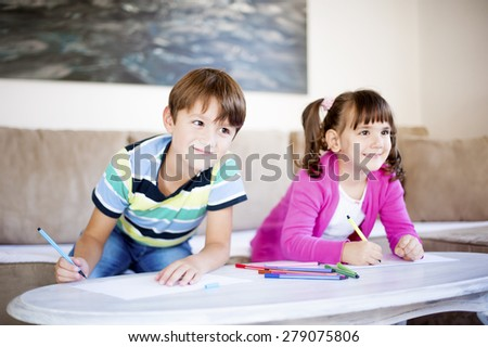Brother and sister playing in the living room. Children drawing - stock photo