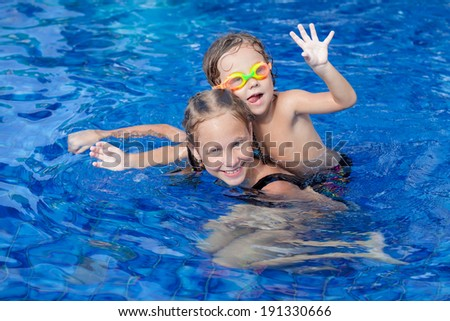 brother and sister playing in the swimming pool - stock photo