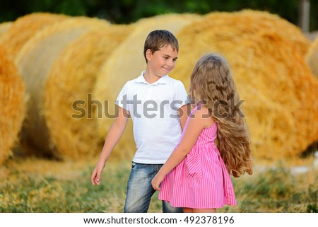 Brother and sister playing in the village on a stack of straw