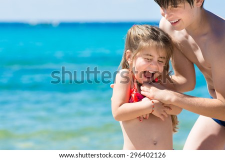 Brother and sister playing on beach vacation, clear and blue sea background - stock photo
