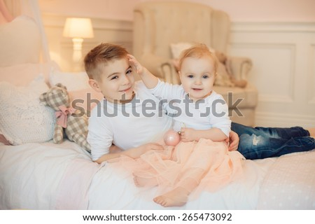brother and sister playing sitting on a bed, cuddling - stock photo