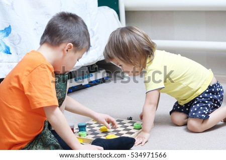 Brother and sister playing together, siblings play home on chess board
