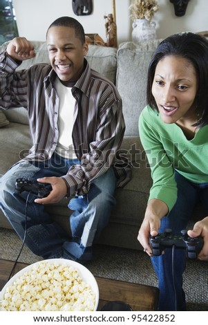 Brother and sister playing video game - stock photo