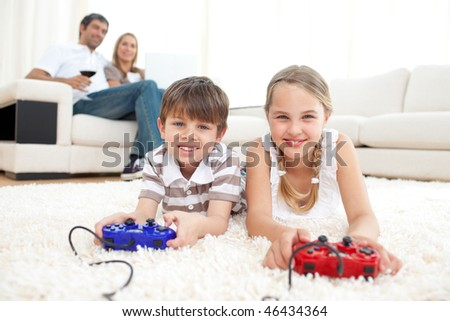 Brother and sister playing video games lying on the floor - stock photo