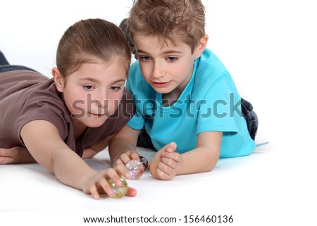 Brother and sister playing with marbles - stock photo