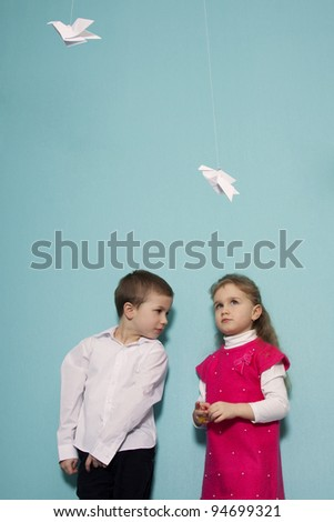 Brother and sister portrait with origami birds - stock photo