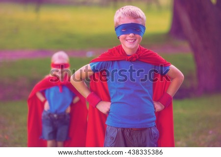 Brother and sister pretending to be superhero in park - stock photo