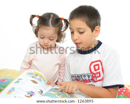 Brother and sister reading a book over a carpet. They look interested and concentrated. Visit my gallery for more images of children - stock photo