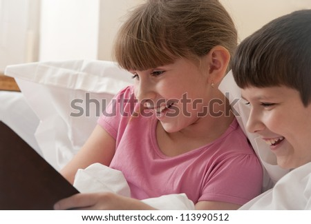 brother and sister, reading book, in bed, close up