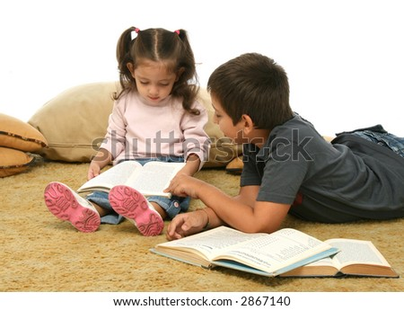 Brother and sister reading books over a carpet. They look interested and concentrated.