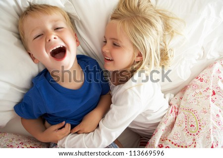 Brother And Sister Relaxing Together In Bed - stock photo