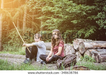 brother and sister resting on a tree trunk - stock photo