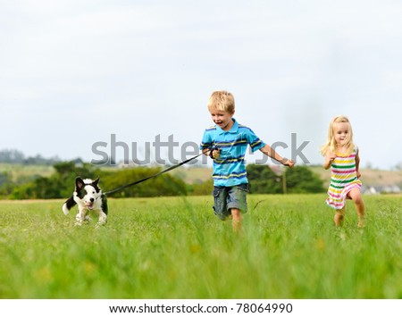 Brother and sister runs in a green field with their new pet