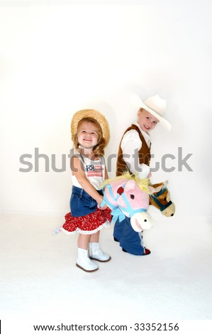 Brother and sister saddle up for a little fun.  Both are dressed in western wear and astride stick ponies. - stock photo