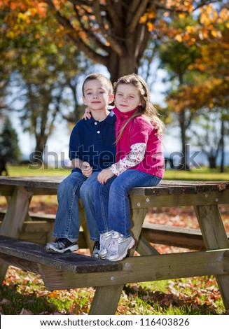 Brother and sister sitting a a bench in the fall - stock photo