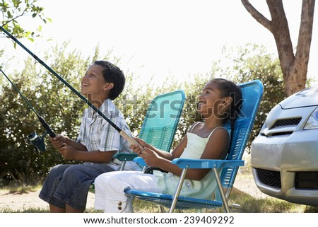 Brother and Sister Sitting in Folding Chairs Holding Fishing Poles - stock photo
